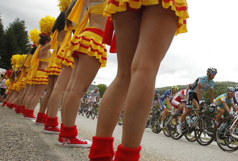 The pack of riders cycles past cheerleaders during the 14th stage of the 99th Tour de France cycling race between Limoux and Foix. (Bogdan Cristel/Reuters)