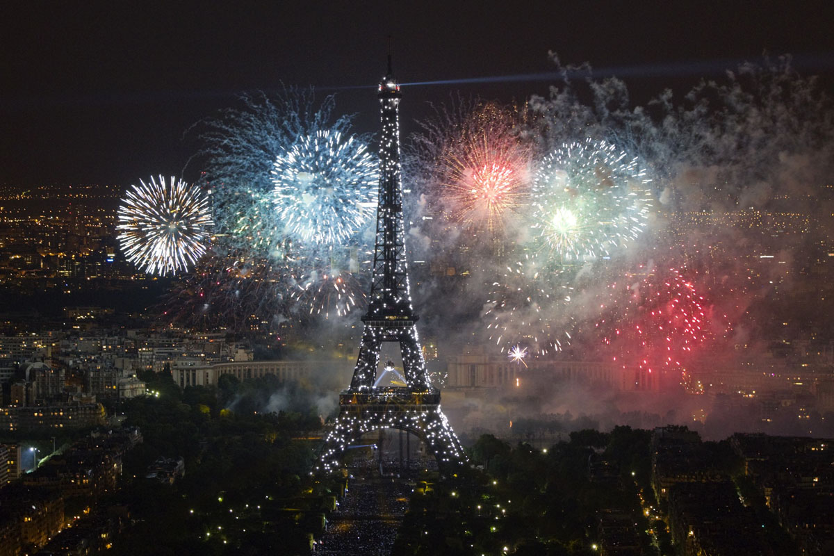 the eiffel tower is illuminated during the traditional bastille day