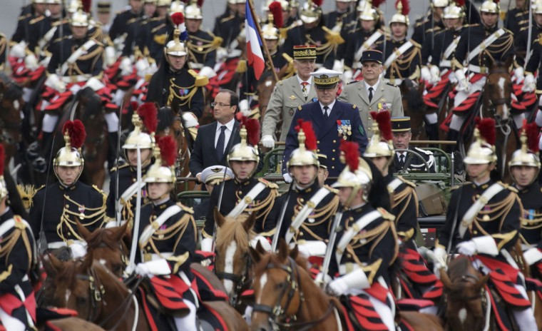 France's President Francois Hollande (centre, L) stands at attention in the command car as he reviews the troops while descending the Champs Elysees in Paris at the start of the traditional Bastille Day military parade in Paris July 14, 2012. (Mal Langsdon/Reuters)