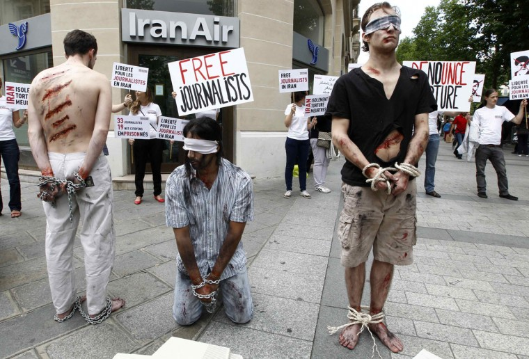Activists from Reporters Without Borders (RSF) with fake injuries and bound hands and feet demonstrate on Champs Elysees Avenue in front of the Iran Air airline company in Paris condemning the imprisonment of journalists and citizen journalists in Iran, and calling for their immediate release. (Jacky Naegelen/Reuters)