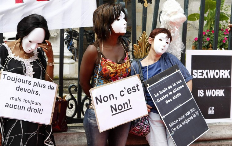 """Prostitutes wearing masks hold placards as they attend a demonstration with sex workers activists against a proposition to abolish prostitution in Lyon July 6, 2012. The French Minister for women's rights wanted to eradicate the sex trade in France and new measures to stamp out prostitution. The placards read """"always more duty but always none right"""" (L), """"no, it's no"""" (C) and """"the noise of the street against the silence of elected representatives. Even with your laws, we will be still there."""" (Emmanuel Foudrotâ€/Reuters)"""