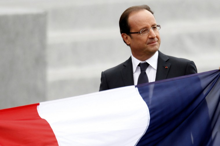 France's President Francois Hollande walks past a French national flag as he leaves the Place de la Concorde after the traditional Bastille Day military parade in Paris July 14, 2012. (Charles Platiau/Reuters)