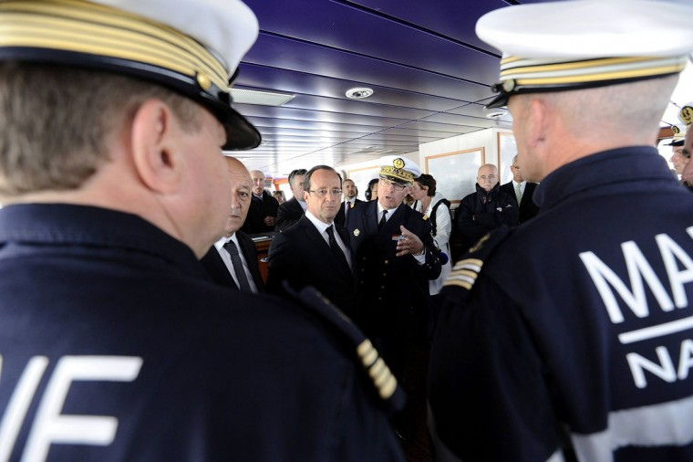 "France's President Francois Hollande (C) listens to high-ranking officers as he visits the High seas salvage tug Abeille Bourbon as part of the Bastille Day celebrations in the seaport of Brest, western France July 14, 2012. Hollande is in Brest to attend ""Les Tonnerres de Brest 2012"" sailing festival. (Jean-Sebastien Evrard/Pool/Reuters)"