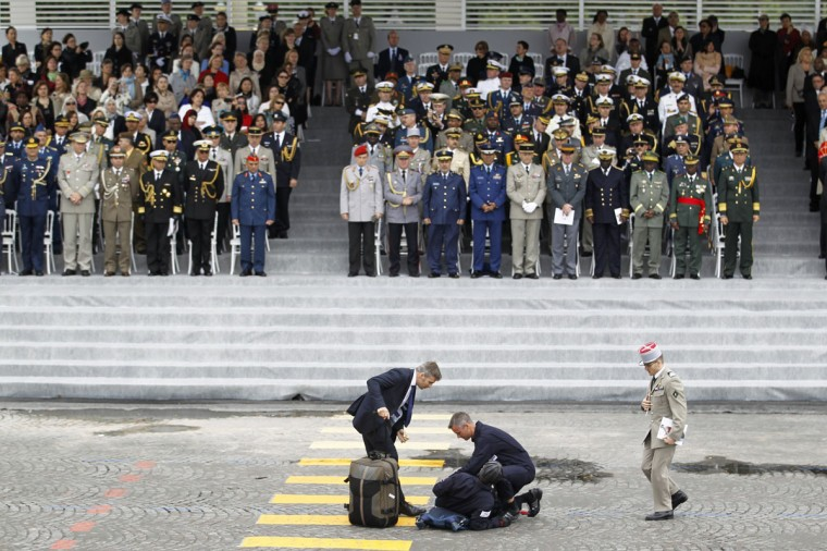An injured parachutist is assisted by medical staff in front of the reviewing stand at the Place de la Concorde during the traditional Bastille Day military parade in Paris July 14, 2012. (Charles Platiau/Reuters)