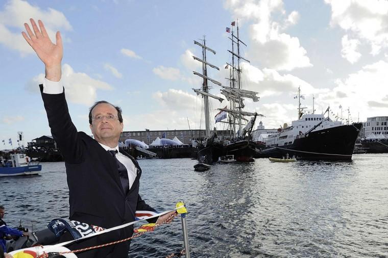 """France's President Francois Hollande waves from a boat during """"Les Tonnerres de Brest 2012"""" sailing festival in the Brest bay, western France July 14, 2012. (Jean-Sebastien Evrard/Pool/Reuters)"""