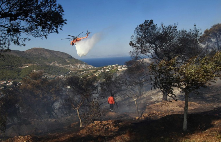 A helicopter drops water over a hill during a forest fire near the town of Keratea, south of Athens. A wildfire swept through forests near Athens on Thursday, forcing residents to use garden hoses and tree branches to keep the flames away from their homes. (John Kolesidis/Reuters)