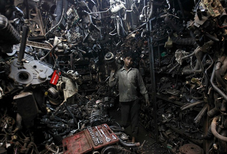 Abdul Samad, 13, carries a part of a used car engine inside an automobile workshop in Mumbai. An Indian automobile industry body on Tuesday slightly lowered its car sales growth forecast for the year ending next March, as higher costs and slower economic expansion impinge on demand. (Danish Siddiqui/Reuters)