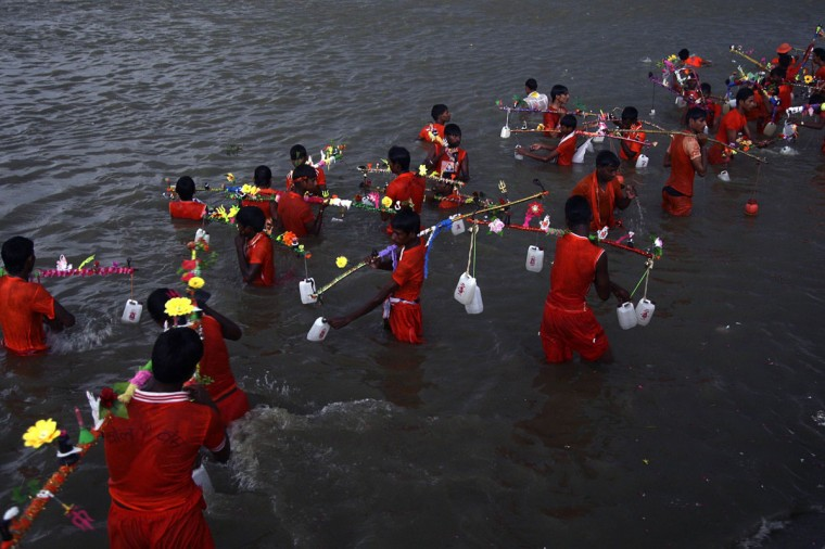Kanwarias or devotees of Hindu god Shiva fill their pots with the water from the river Ganges in the northern Indian city of Allahabad. Hundreds of the Kanwarias carry holy water from the Ganges to their hometowns to be offered to Shivling (a symbol of Lord Shiva). (Jitendra Prakash/Reuters)
