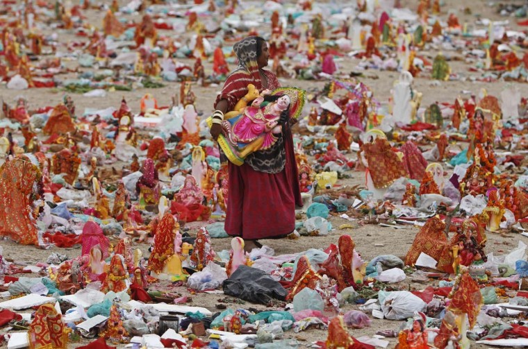 A woman carries an idol of Hindu goddess Dashama on the banks of the river Sabarmati, in the western Indian city of Ahmedabad July 29, 2012. Hindu devotees keep the idols in their house for 10 days for the Dashama festival, before immersing them in the Sabarmati river on the tenth night. (Amit Dave/Reuters)