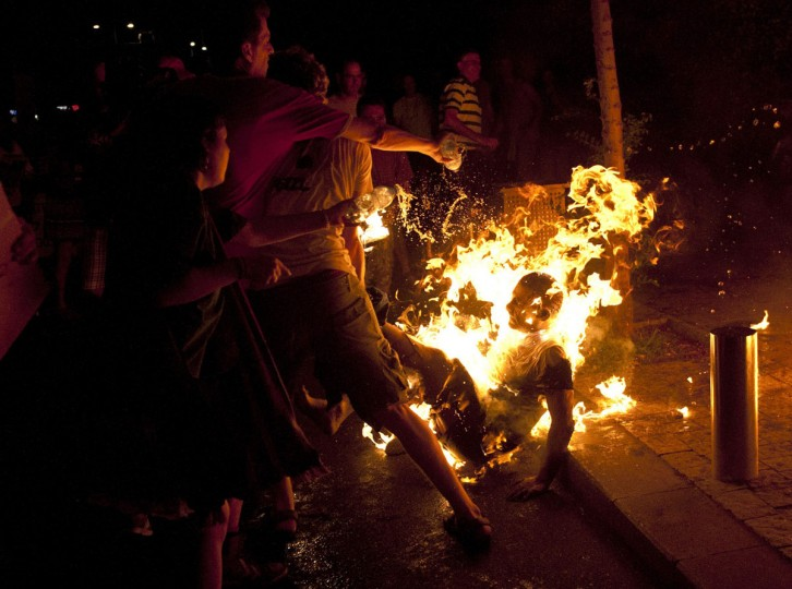 "Protesters try to extinguish flames from a protester after he set himself on fire during a demonstration calling for social justice in Tel Aviv July 14, 2012. Some thousands of Israelis gathered in cities throughout the country to mark one year since the start of social protests demanding for more social welfare, local media reported. The protester, who is critically injured, is receiving medical attention after he poured gasoline on his body and set himself on fire. In a letter he left behind, he wrote ""The state of Israel robbed me,"" according to news reports. (Ben Kelmer/Reuters)"