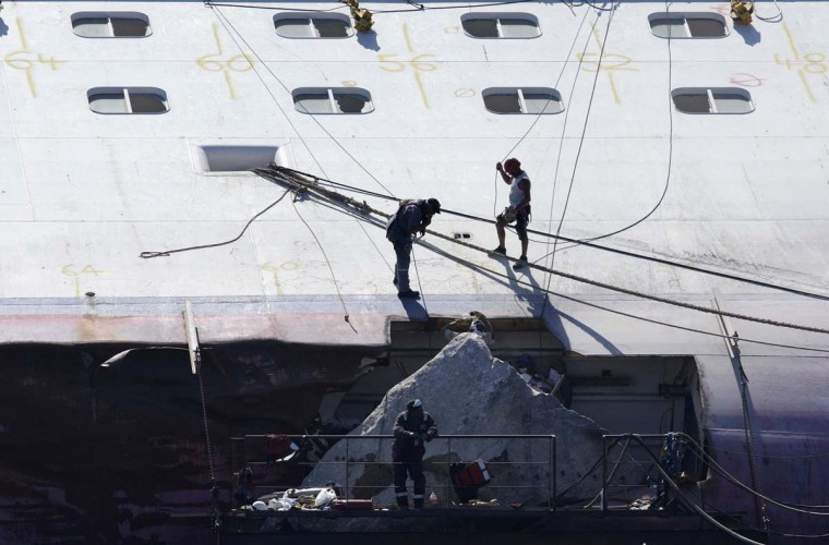 Workers prepare to remove a giant rock embedded in the hull of the capsized cruise liner Costa Concordia near the harbour of Giglio Porto. Part of the rock will be used as a memorial for the 32 people who died when the cruise liner slammed into the coastline off the island of Giglio. (Remo Casilli/Reuters photo)