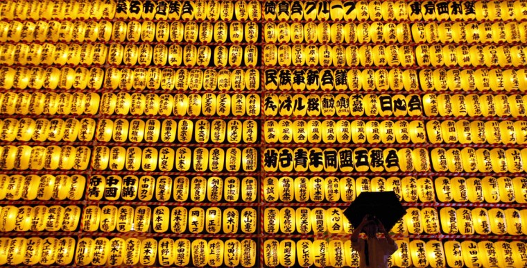 A visitor takes a pictures while holding an umbrella in front of paper lanterns during the annual Mitama festival at the Yasukuni Shrine in Tokyo. About 3,000 paper lanterns are lit to comfort the souls of dead during the annual festival at the shrine where more than 2.4 million war dead are enshrined. (Issei Kato/Reuters)
