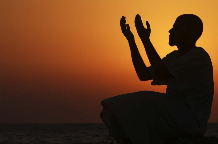 A man raises his hands to pray near the sea at sunset after a day of fasting in the holy month of Ramadan in Benghazi July 24, 2012. (Esam Al-Fetori/Reuters)
