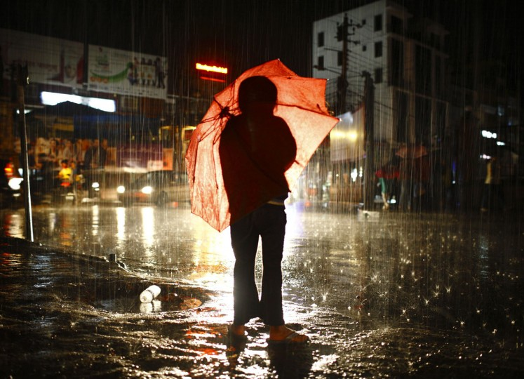 A girl with her umbrella waits to cross the road during rainfall in Kathmandu. The monsoon season in Nepal typically lasts from June to August. (Navesh Chitrakar/Reuters)
