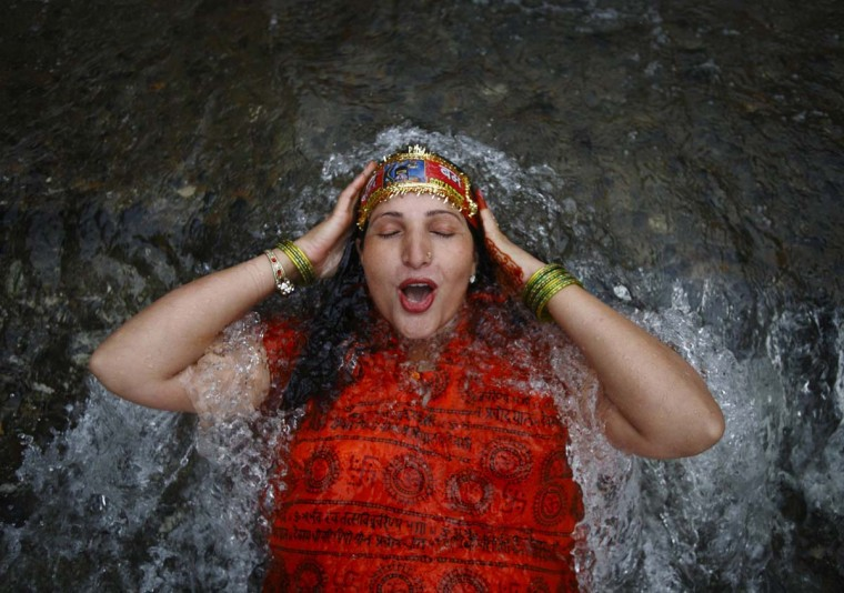 "A Hindu devotee takes a dip at the Bagmati River while she takes part in the ""Bol Bom"" (or Say Shiva) pilgrimage in Kathmandu. The faithful, chanting the name of Lord Shiva, run some 15 km (9 miles) barefooted to Pashupatinath temple seeking good health, wealth and happiness. (Navesh Chitrakar/Reuters photo)"