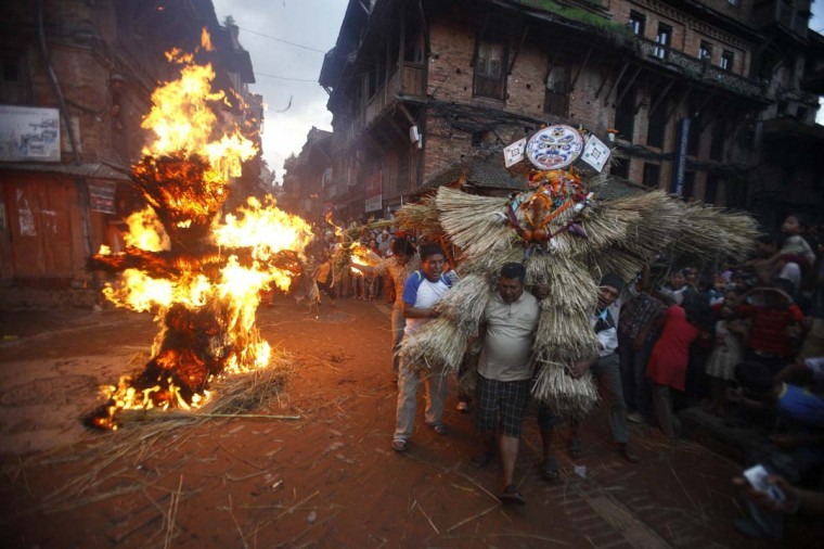 "People carry an effigy of demon Ghantakarna as another effigy of the demon is burnt to symbolize the destruction of evil, during the Ghantakarna festival in the ancient city of Bhaktapur. According to legend, the demon is believed to ""steal"" children and women from their homes and localities. (Navesh Chitrakar/Reuters photo)"