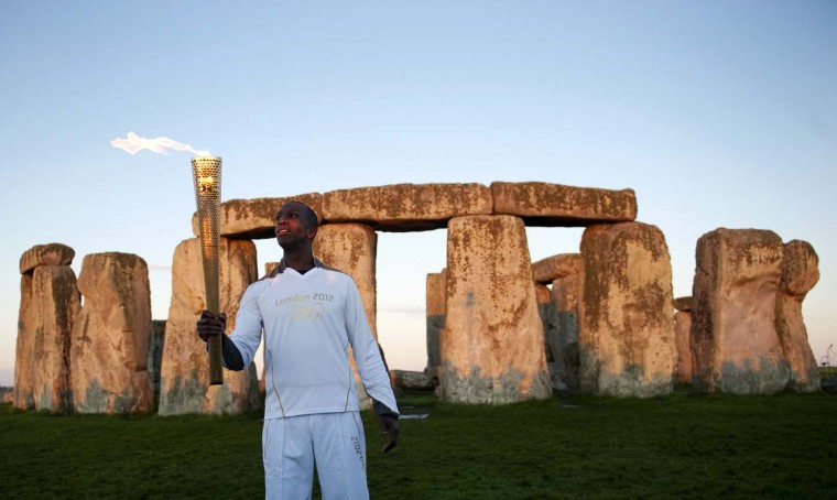 JULY 12: Olympic gold medalist and Torchbearer Michael Johnson holds the Olympic Torch at Stonehenge, a World Heritage site, in Salisbury, southern England July 12, 2012. (Kieran Doherty/Reuters)