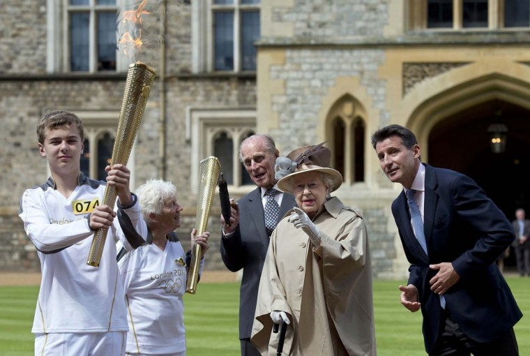 JULY 10: Britain's Queen Elizabeth, Prince Philip, LOCOG Chairman Sebastian Coe (R) and Olympic torch bearer Gina Macgregor (2nd L) watch as torchbearer Phil Wells takes the Olympic Flame at Windsor Castle. (Ben Stansall/Reuters)