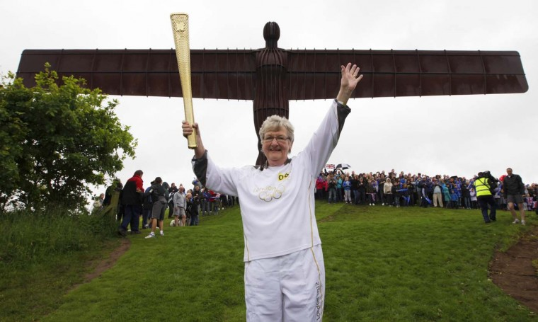 JUNE 16: Torch bearer Iris Hutchinson waves while holding a London 2012 Olympic Games torch at the Angel of the North sculpture near Gateshead, north east England. (David Moir/Reuters)