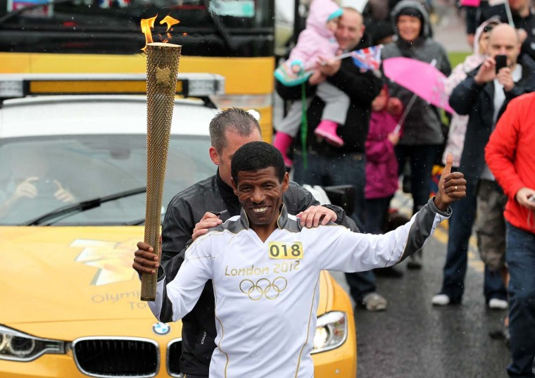 JUNE 16: Ethiopian Olympic gold medal winner Haile Gebrselassie carries a London 2012 Olympic Games torch between Gateshead and South Shields in north east England. (LOCOG via Reuters)