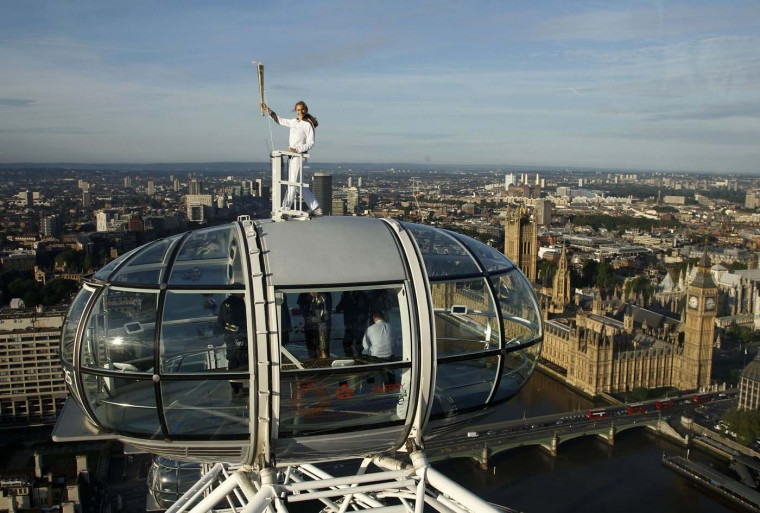 LONDON, UNITED KINGDOM - JULY 22: Torch bearer Amelia Hempleman-Adams, age 17, stands on top of a capsule on the London Eye as part of the torch relay ahead of the London 2012 Olympic Games in London July 22, 2012. (Luke MacGregor/Reuters)