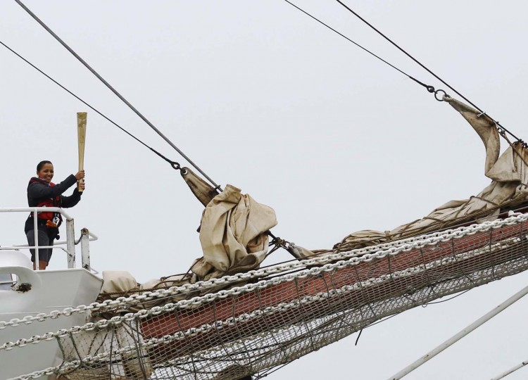 DOVER, UNITED KINGDOM - JULY 18: Torch security officer Sakira Suzia carries the Olympic torch into harbour on board the tall ship Stavros S Niarchos after the official torch carrier Jamie Clarke became seasick at Dover in south east England July 18, 2012. (Luke MacGregor/Reuters)
