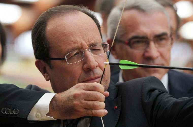 France's President Francois Hollande (L) prepares to shoot an arrow during a visit to meet members of France's 2012 London Olympics team at the training headquarters of INSEP (National Institute for Sport and Physical Education) in Paris. (Charles Platiau/Reuters photo)