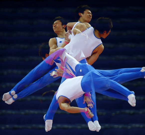 South Korea's Kim Soo-myun rotates above the horizontal bar during men's gymnastics podium training before the 2012 London Olympic Games in London July 25, 2012. Picture taken with multiple exposures. (Mike Blake/Reuters)
