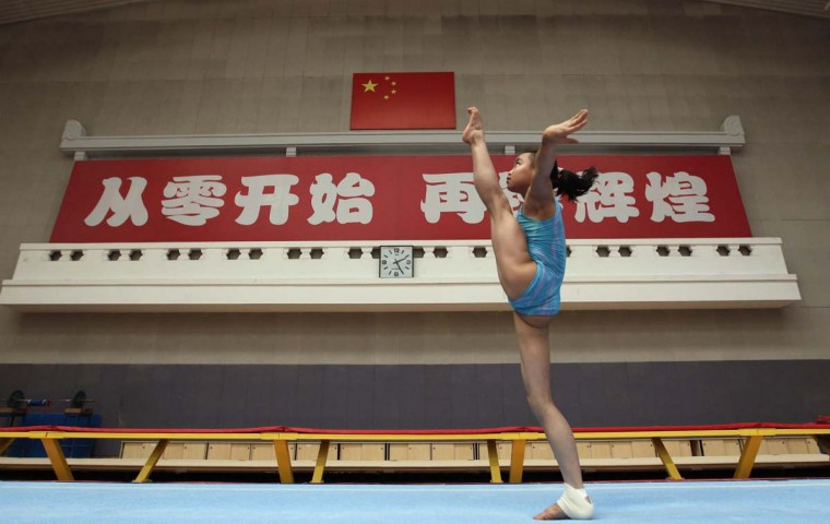"A gymnast from the Chinese national gymnastics team practices during a training session at General Administration of Sport of China, in Beijing. These young gymnasts are training for the Rio de Janeiro 2016 Olympic Games. The Chinese characters on the wall read, ""Starting from scratch, Creating greater glories"". (Jason Lee/Reuters photo)"