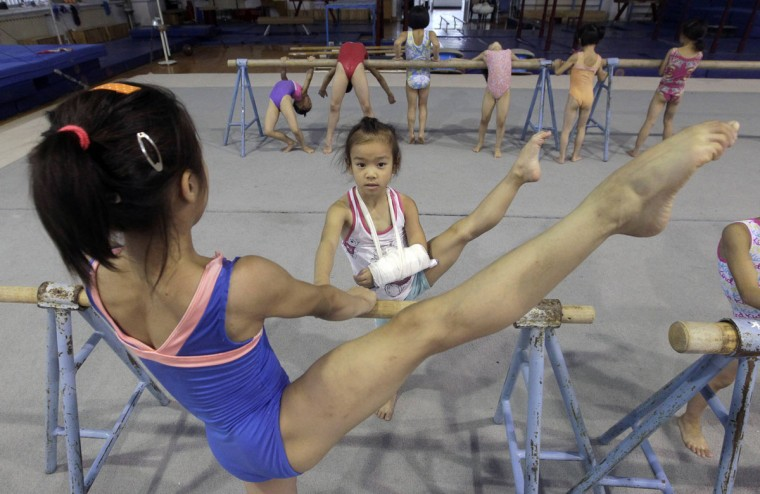 Young gymnast Mo Yuxin (C), who broke her arm during a training, practice basic skills with other gymnasts at a juvenile gymnastics training base in Wuhan, Hubei province in China. (Stringer/Reuters)