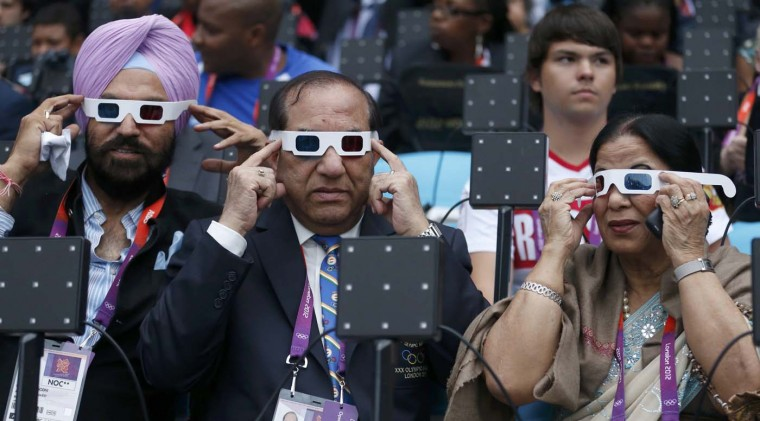 Acting Indian Olympic Association President Vijay Kumar Malhotra (C), his wife Krisha Malhotra (R) and guest Gurmit Singh (L) of India try on their glasses as they sit in the VIP box before the opening ceremony of the London 2012 Olympic Games at the Olympic Stadium July 27, 2012. (Suzanne Plunkett/Reuters)