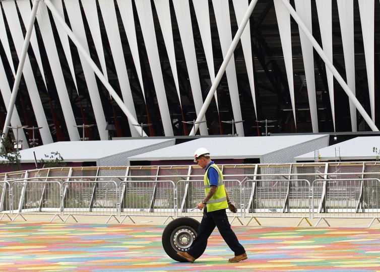 A worker pushes a tyre past the Olympic Stadium in the London 2012 Olympic Park at Stratford in London. (Luke MacGregor/Reuters photo)