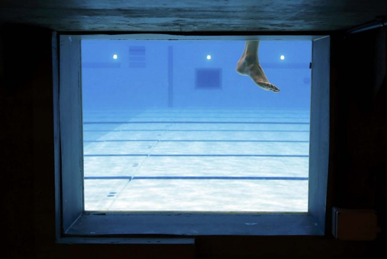 A swimmer rests during a training session at the main pool of the Aquatics Centre before the start of the London 2012 Olympic Games in London July 25, 2012. (David Gray/Reuters)