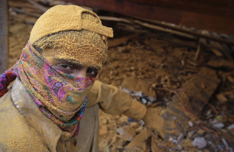 A labourer, his face covered in sawdust, pauses, as he is photographed during a break, during the overhauling of a wooden cargo ship in Karachi's Fish Harbour. The process of overhauling a boat takes about a week, in which the boat is brought to dry land and its wooden panels and paint serviced by a team of 20 carpenters and labourers, before it is set back to sea. (Akhtar Soomro/Reuters)