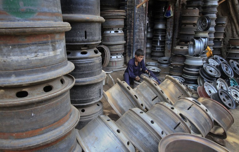 A boy uses a sandpaper to clean old tyre rims to be reused at a workshop in Lahore, Pakistan. (Mohsin Raza/Reuters)