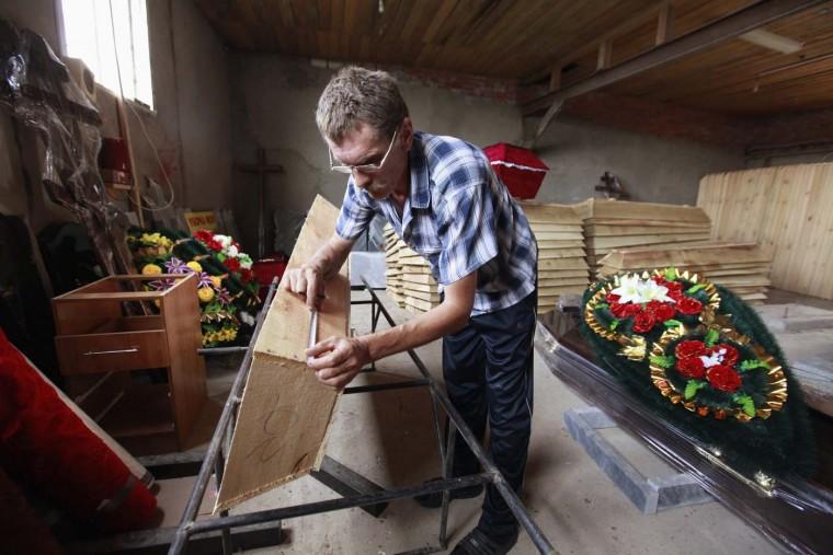 An employee of a workshop works on a coffin at a city cemetery in the town of Krymsk in Krasnodar region, southern Russia, July 8, 2012. (Eduard Korniyenko/Reuters)