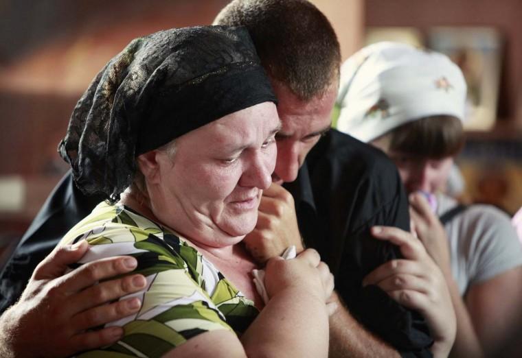 Acquaintances of Pyotr Ostapenko, 35, a flood victim, mourn inside a church during a religious ceremony before the funeral in the village of Moldavanskoye outside Krymsk in Krasnodar region, southern Russia, July 8, 2012. (Eduard Korniyenko/Reuters)