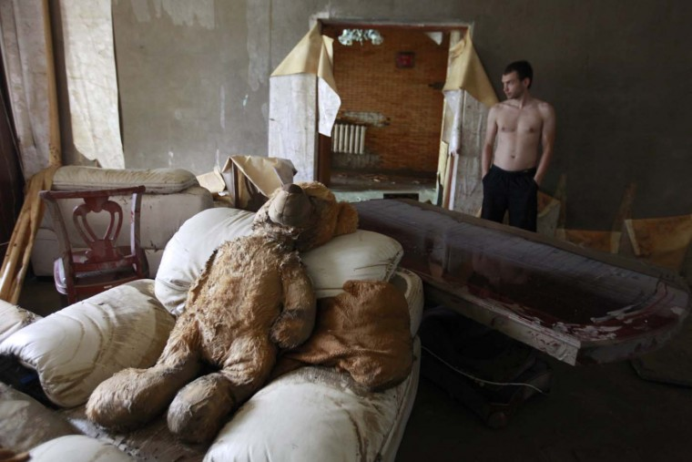 A man stands inside a house damaged by floods in the town of Krymsk in the Krasnodar region, southern Russia, July 8, 2012. Russian President Vladimir Putin ordered investigators to find out if enough was done to prevent 144 people being killed in floods in southern Russia after flying to the region to deal with the first big disaster of his new presidency. (Eduard Korniyenko/Reuters)