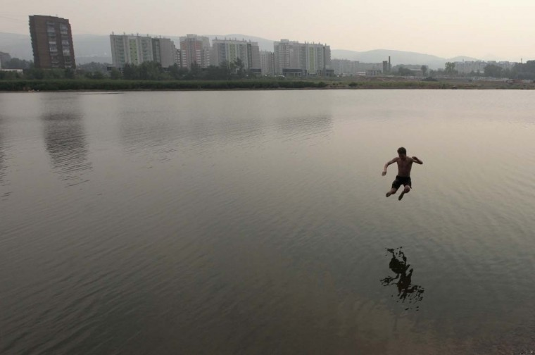 A man jumps into the waters of the Yenisei River in Russia's Siberian city of Krasnoyarsk, July 25, 2012. (Ilya Naymushin/Reuters)