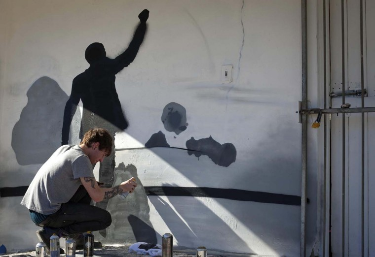 A volunteer paints a mural depicting the life of former President Nelson Mandela at a library in Cape Town's Imizamo yethu township, July 18, 2012. Thousands of South Africans heeded the call to offer 67 minutes of their time to help build communities as part of celebrations of Mandela's 94 birthday today. (Mike Hutchings/Reuters)
