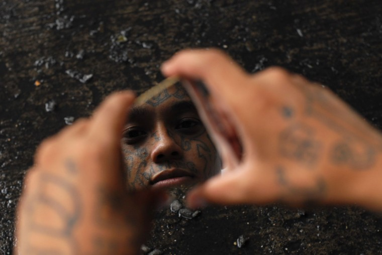 "A gang member looks into a broken piece of mirror while getting a haircut by a fellow inmate at a prison in Quezaltepeque, on the outskirts of San Salvador June 2, 2012. The relentless tit-for-tat murders between El Salvador's two largest street gangs - ""Calle 18"" and ""Mara Salvatrucha"" - made the country the most murderous in the world last year after neighboring Honduras, also ravaged by gang violence. That was until Garcia, from the Calle 18 (""18th Street"") gang, along with elders from the Mara Salvatrucha, declared an unprecedented truce that authorities say has cut the homicide rate in half in just four months. (Ulises Rodriguez/Reuters)"