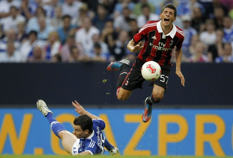 AC Milan's Mattia Valoti (R) is challenged by Schalke 04's Alexander Baumjohann during their friendly soccer match in Gelsenkirchen. (Alex Domanski/Reuters)