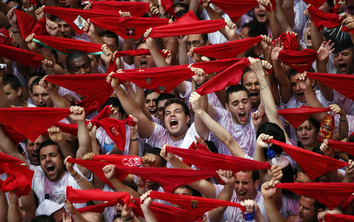 "Revellers hold up their red scarves during the start of the San Fermin Festival in Pamplona July 6, 2012. The annual festival, best known for its daily running of the bulls, kicked off on Friday with the traditional ""Chupinazo"" rocket launch and will run until July 14. (Susana Vera/Reuters photo)"