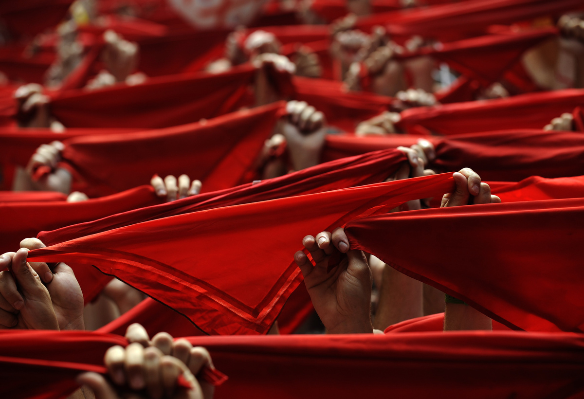 "Revellers hold up their red scarves during the start of the San Fermin Festival in Pamplona July 6, 2012. The annual festival, best known for its daily running of the bulls, kicked off on Friday with the traditional ""Chupinazo"" rocket launch and will run until July 14. (Eloy Alonso/Reuters photo)"