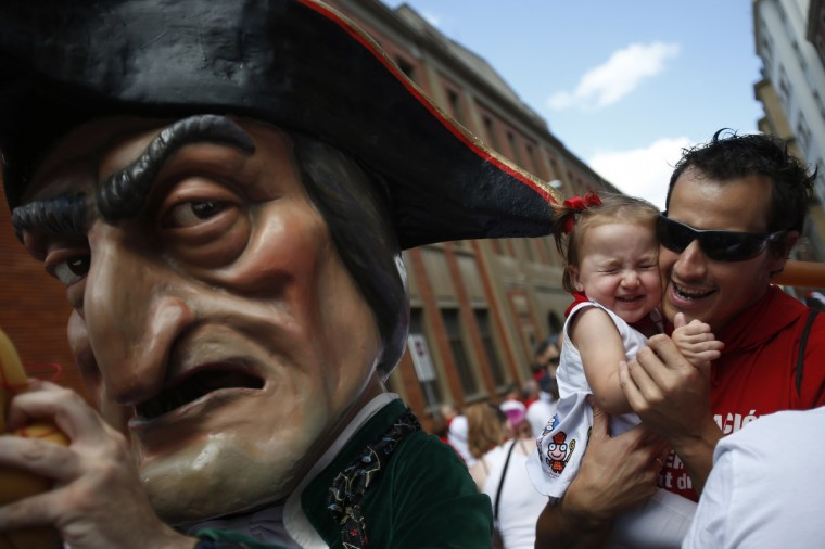 "A girl reacts as she gets hit by the hat of a ""Kiliki"" during San Fermin festival's ""Comparsa de gigantes y cabezudos"" (Parade of the giants and the big heads) in Pamplona. ""Kilikis"", wearing outsized masks as they playfully hit bystanders with sponges on sticks, parade daily through the city accompanied by brass bands during the nine-day-long festival made popular by U.S. writer Ernest Hemingway. (Susana Vera/Reuters photo)"