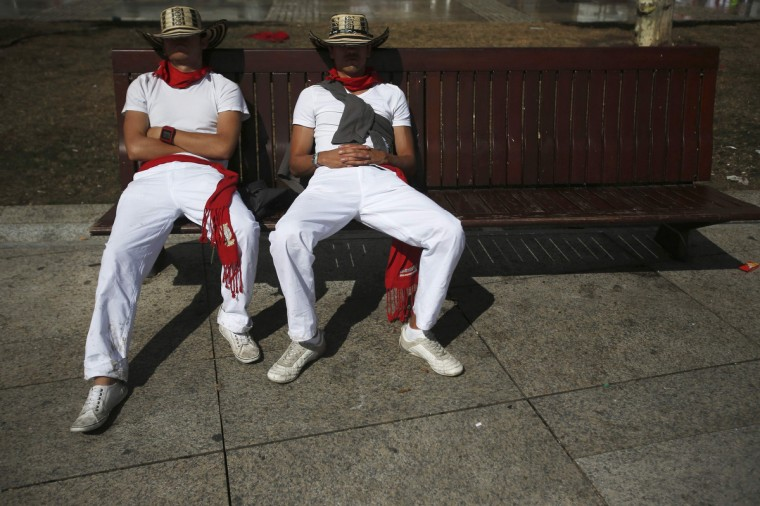 Revellers sleep on a bench after the second running of the bulls during the San Fermin festival in Pamplona. (Susana Vera/Reuters photo)