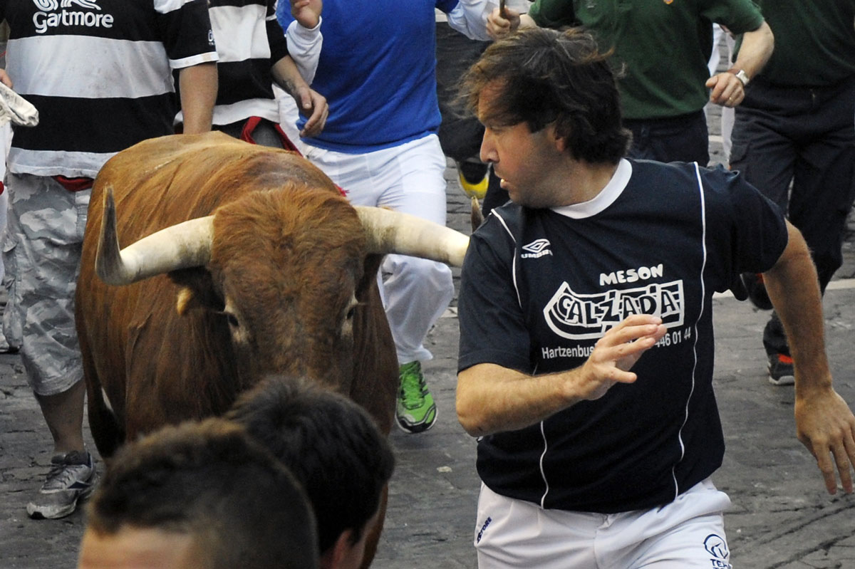 Runners sprint in front of Cebada Gago fighting bulls at Telefonica corner during the second running of the bulls of the San Fermin festival in Pamplona July 8, 2011. (Vincent West/Reuters photo)
