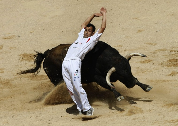 A recortador performs a pass during a contest at Pamplona's bullring on the third day of the San Fermin festival. (Joseba Etxaburu/Reuters photo)