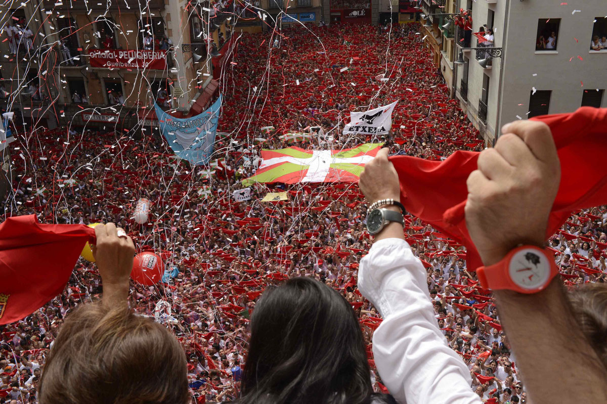 """Revellers on the town hall balcony hold up red scarves during the start of the San Fermin Festival in Pamplona July 6, 2012. The festival, best known for its daily running of the bulls, kicked off on Tuesday with the traditional """"Chupinazo"""" rocket launch and will run until July 14. (Vincent West/Reuters photo)"""