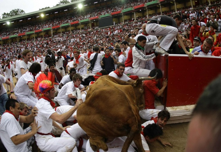 A wild cow leaps over a group of revellers following the third day of the running of the bulls at the bullring during the San Fermin festival in Pamplona . Various runners suffered light injuries in a run that lasted two minutes and twenty-eight seconds, according to the Navarran government press office. (Joseba Etxaburu/Reuters photo)